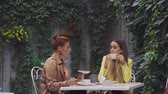 average age : A middle-aged red-haired woman in a brown coat and a brown-haired young woman in a yellow coat are sitting in a summer street cafe, chatting with each other and drinking coffee. Close-up.