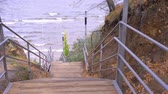ahornbaum : Descent down a steep wooden staircase. The camera moves along a wooden staircase down to the water in an autumn park. Stock Footage