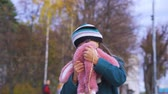 vista aérea : Portrait of a laughing teenage girl with glasses, in a dark turquoise coat, in a knitted hat and a pink bag with a backpack in the form of a soft toy. The girl enjoys the new backpack. Autumn day.