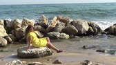 Woman sits on stone on sea shore Стоковые видеозаписи