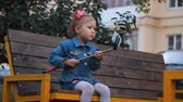 kacérkodás : cute funny beautiful little girl sitting on bench in park and doing selfie on white mobile phone. A child makes a selfie photo.