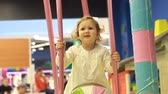 hysterics : Cute child on the playground plays different games and rides on the carousel. Little girl capricious, crying and hysterical. A little pretty girl will express discontent, upset and anger. Stock Footage
