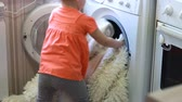 linho : Funny cute little girl puts dirty things in the washing machine. Baby and laundry.