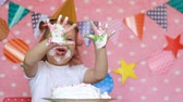 лизать : Dirty hands of a child in a cake. Birthday and party. Funny girl licks her fingers with dessert