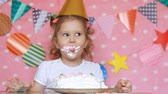 лизать : Happy birthday. A cute little girl eats a cake with dirty face and hands. A child eating a dessert at a table. Close-up portrait
