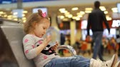 espera : Child in an airport terminal sitting in the waiting room playing with a mobile phone as they wait for their flight. A nice little girl uses a game application on a smartphone.