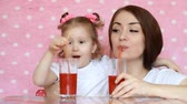 vegetarianismo : Mother and daughter drink smoothies through a straw and smile. Close-up portrait of a young woman with her baby who enjoy a refreshing delicious drink. Pink background Stock Footage