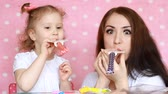 cheerfully : Mother and daughter blowing horns, smile, have fun, laugh and celebrate. Happy birthday. Party. A woman and her child. Close-up portrait on pink background. Stock Footage
