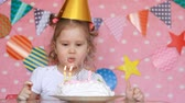 três pessoas : A child girl blows out candles on a birthday cake and eats it with his finger. Baby makes a wish