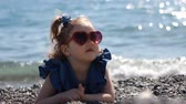 outing : A child by the sea on a pebble beach on a windy sunny day with glasses in the form of a heart