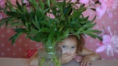 piwonie : Child girl hides in a with peonies. Baby playing with pink peony flowers. Wideo