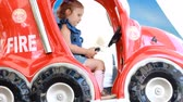 fire truck : Child girl and rides an fire car in the park for entertainment. Attractions for children. Stock Footage