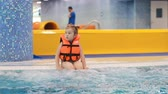 vesta : Child girl in the pool in the life jacket sits in the boiling blue water and is preparing to dive
