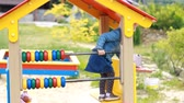 szórakozási : Child girl plays in the playground in different games. Entertainment for children.