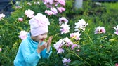 piwonie : Child girl is playing in the garden with peonies. Happy baby covers his face with his hands and hides in peony.