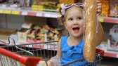 депо : Child girl sits in a trolley for products in the store and holds a baguette. Baby shopping
