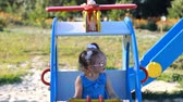 eğlenmek : Child girl is riding a carousel helicopter in an amusement park. Baby plays in the playground. Stok Video