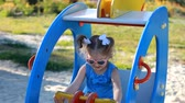 playground : Child girl is riding a carousel helicopter in an amusement park. Baby plays in the playground. Stock Footage