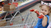 baby store : Child girl in the supermarket buys food with trolley for products. Baby shopping.