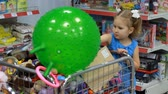 baby store : Child girl in the supermarket chooses a toy for himself. Baby shopping.