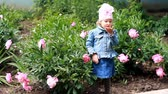 nose : Child girl send air kisses. Garden with peonies and funny baby
