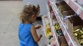 депо : Child in the supermarket buys candies and sweets. Shopping store