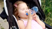 baby carriage : Child girl lies in a baby carriage and drinks water from a bottle. Thirst in summer.