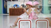 bekliyor : Child tourist in an airport terminal sitting in the waiting room playing with a mobile phone as they wait for their flight. Little girl uses a game application on a smartphone.