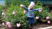 piwonie : Child girl poses for a photo as a model and dances in the peony garden.