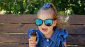 eats : Child girl in sunglasses is eating ice cream while sitting on a bench in the park on a sunny summer day. Portrait of a baby close-up.