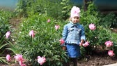 piwonie : Child girl send air kisses. Garden with peonies and funny baby