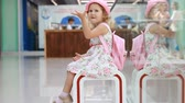 waiting : Child girl tourist at the airport waits for his flight of travel and sings a song. Stock Footage
