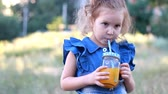 vegetarianismo : Child drinks orange fresh in the summer. Portrait of a little girl who enjoys smoothies through a tube Stock Footage