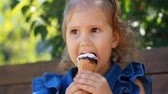 zaměřit se na popředí : Child girl eats ice cream cone with chocolate In the park on a sunny summer day. Portrait of a baby close-up.