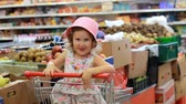 депо : Shop discounts. Sale. Child girl in a supermarket sits in a shopping cart. Стоковые видеозаписи