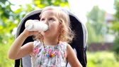 natural yogurt : Child girl sits in a stroller and drinks a milk drink from a bottle or kefir.