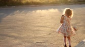 oeuvre : Child girl sings into a microphone a song in the rays of a sunset in the summer.