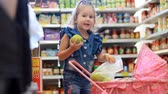 депо : Child girl in the store makes purchases. Mother with child buys fruit. Стоковые видеозаписи