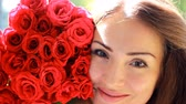 kacérkodás : Portrait of a young beautiful woman with a bouquet of flowers of red roses.