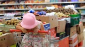 gastos : Child girl in the store chooses fruit. Grocery supermarket and shopping trolley Stock Footage