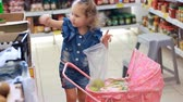 vegeterian : Child girl in the store makes purchases. Mother with child buys fruit. Stock Footage