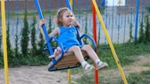 plac zabaw : Sad child girl swings on the playground Wideo