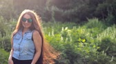sunbeams : Beautiful girl with very long hair in the sunglasses enjoying a sunny summer afternoon at sunset.