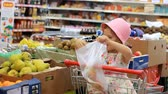 vegeterian : Child girl in the store chooses fruit. Grocery supermarket and shopping trolley Stock Footage