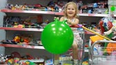 carrito de bebe : Childrens shop with toys. A child in a supermarket sits in the shopping cart