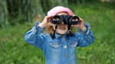 espião : Child girl looking through binoculars and watching the nature