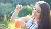 vegetarianismo : Woman drinks smoothies or orange fresh outdoors.