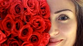 kacérkodás : Face close-up of a beautiful young woman with red roses. Advertising. Advertisement.