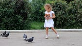 mák : Child girl is feeding birds of pigeons and eats a loaf in the park.