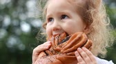 буханка : Child girl eating loaf with poppy seeds outdoor.